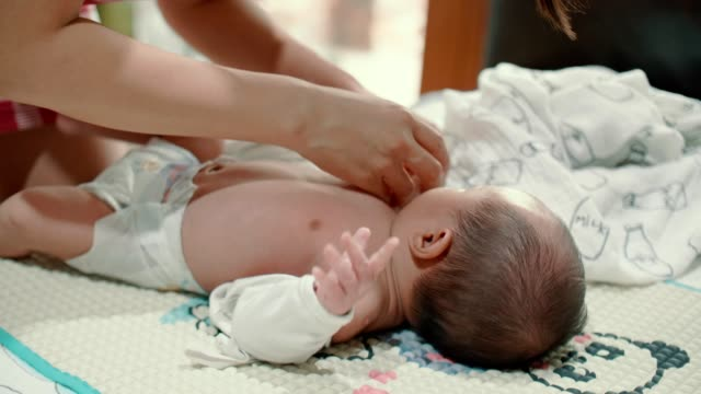 caring mother getting dressed her little newborn baby boy(0-1 months) at home - 0 1 months stock videos & royalty-free footage