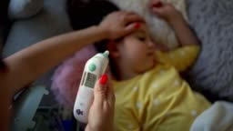 Caring mother measuring her daughter temperature with digital thermometer and she is healthy now