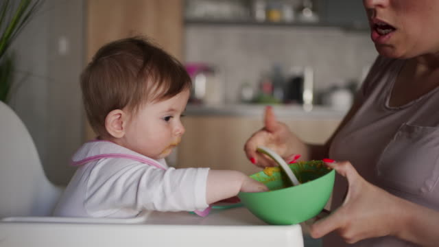 caring mother trying to feed her baby girl while she making a mess with baby food - feeding stock videos & royalty-free footage