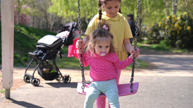 caring older sister swinigng her toddler sister on a swing at the playground in public park making sure she is safe - sister stock videos & royalty-free footage