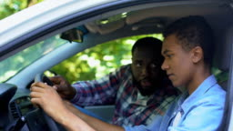 Caring parent teaching son how to drive car, spending time together, family