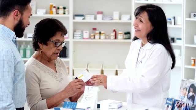 vídeos de stock, filmes e b-roll de o farmacêutico de inquietação discute a medicina com cliente sênior - perguntando