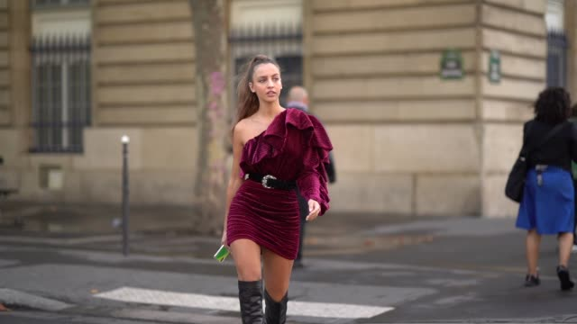 stockvideo's en b-roll-footage met carla ginola wears a lustrous burgundy with tiny polka dots frilly oneshoulder gathered mini dress a black belt with a silver buckle black kneehigh... - stippen