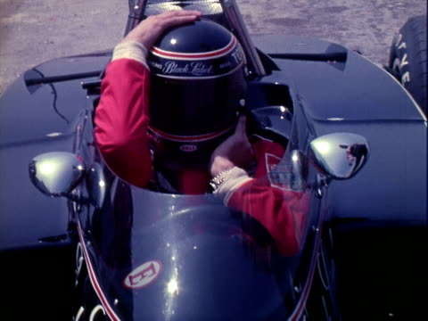 Carling Racing Team crew pushing Black Label sponsored Lola T330 Chevrolet V8 along pits at Riverside International Raceway race car driver TONY...