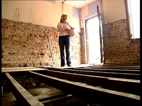 stockvideo's en b-roll-footage met cumbria carlisle exposed floorboards in room of house which was flooded in january 2005 as door opens and homeowner nicola moore enters ms nicola... - houten vloer
