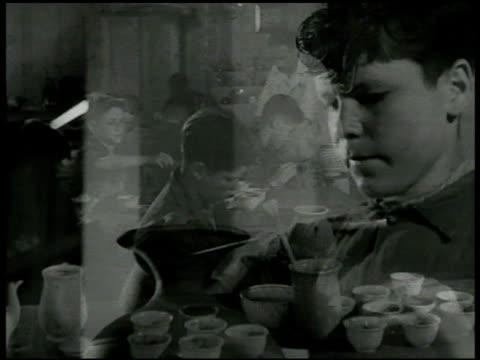vídeos de stock e filmes b-roll de 'carlo' at potter's wheel working w/ large clay vase ms boy's feet working potter's wheel 'carlo' painting small vase instructor showing another... - jarra recipiente