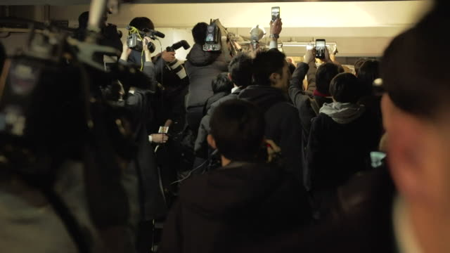 vidéos et rushes de carlos ghosn in a car surrounded by reporters during his trial in tokyo - ghosn