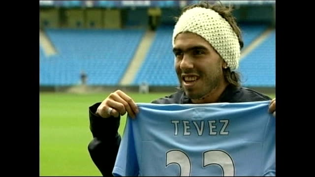 vidéos et rushes de carlos tevez suspended for two weeks for refusing to play in champions league match; lib tevez posing with manchester city shirt for press photocall... - vêtement de peau
