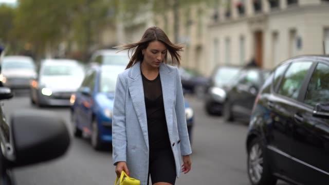 Carlotta Rubaltelli wears a yellow balenciaga triangle bag a gray jacket a black dress with mesh Vans socks black heels shoes outside Valentino...