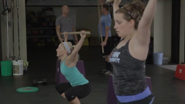 vídeos y material grabado en eventos de stock de carly and tali perform dowl squat warm-ups. - forma de barra