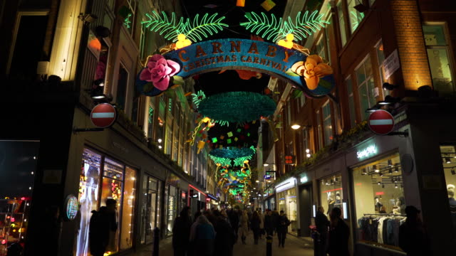 carnaby street busy with christmas shoppers and carnival style christmas lights - street style点の映像素材/bロール