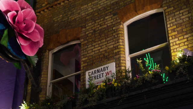 Carnaby Street sign with flower boxes and floral decorations at night