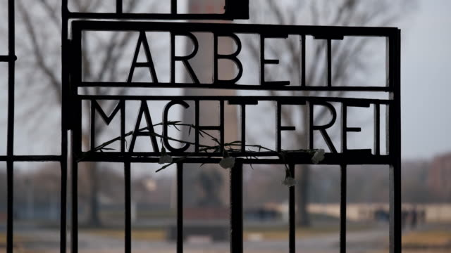 """carnations hang at the infamous entrance gate that reads: """"arbeit macht frei"""", or """"work sets one free"""" at the sachsenhausen concentration camp... - infamous stock videos & royalty-free footage"""