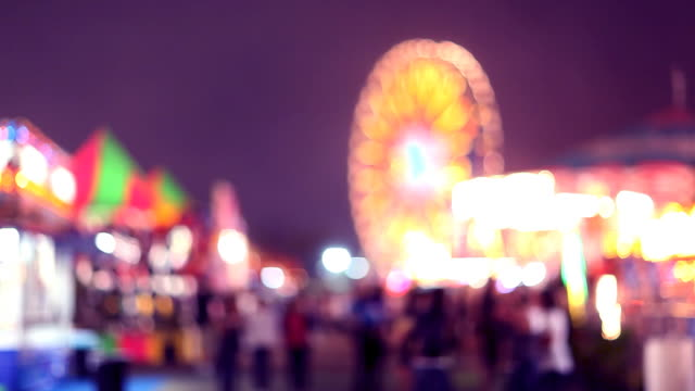 carnival rides and games at night (defocused) - halvbild bildbanksvideor och videomaterial från bakom kulisserna