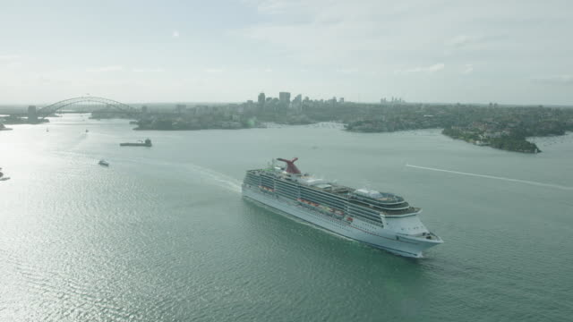 carnival sprit cruise ship in sydney harbour pull out to see sydney cbd and opera house behind swing around ship to see fort denison and sydney... - bennelong point stock videos and b-roll footage