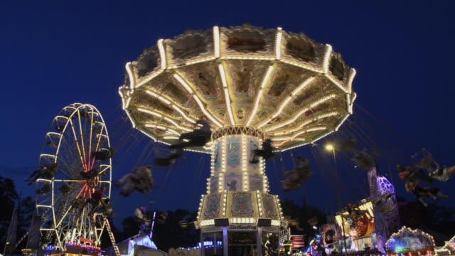 vidéos et rushes de ws carnival swing ride carousel at dusk in public festival / landshut, bavaria, germany - fête foraine