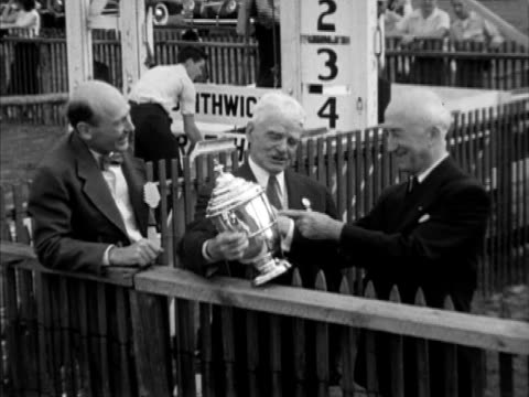 Carolina Cup ad in newspaper TU WS Racehorse walking FG people BG Two unidentified men Governor James Byrnes holding trophy VS Race crowd people...
