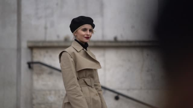 caroline daur wears a black beret hat, a trench coat, a red bag, white boots, outside giambattista valli, during paris fashion week womenswear... - street style stock videos & royalty-free footage