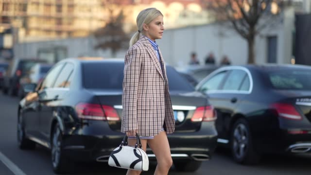 caroline daur wears a checked oversized blazer jacket, a prada white and black bag, pink wool socks, red shoes, a blue striped shirt, outside prada,... - street style stock videos & royalty-free footage