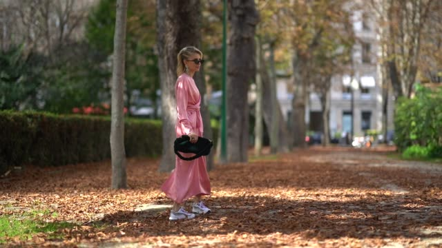 caroline daur wears a pink dress, sneakers, sunglasses, a bag, outside issey miyake, during paris fashion week womenswear spring/summer 2018, on... - street style stock videos & royalty-free footage