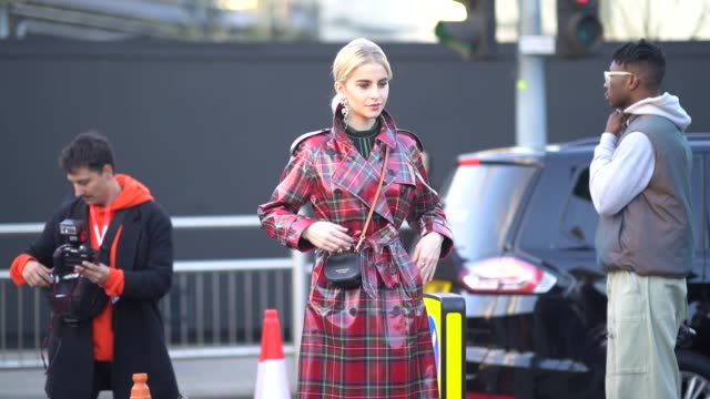 Caroline Daur wears a red checked PVC trench coat a black Burberry bag outside Burberry during London Fashion Week February 2018 on February 17 2018...