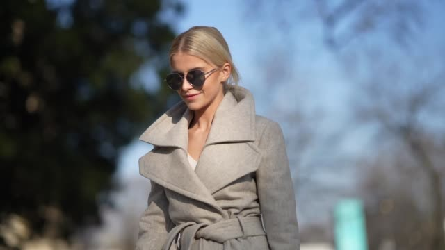 stockvideo's en b-roll-footage met caroline daur wears mirror sunglasses, a gray long wool coat, a small bag, fringed high heeled shoes, outside elie saab, during paris fashion week -... - zoom out