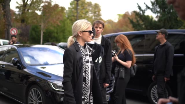caroline daur wears sunglasses a black long coat a black and white side slit dress with printed geometric patterns a scarf black leather boots... - white stock videos & royalty-free footage