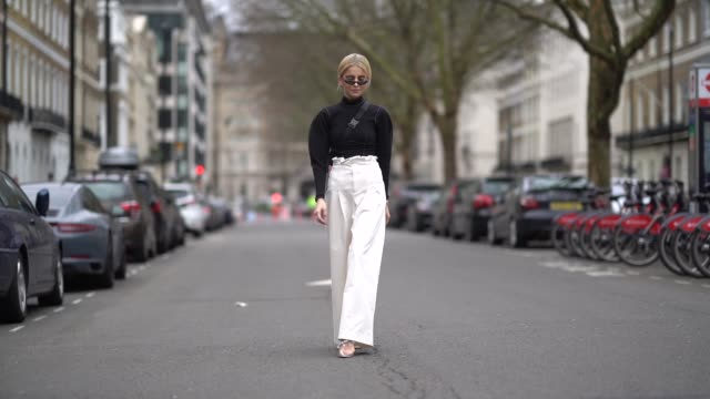 Caroline Daur wears sunglasses a black top white large flare pants a shoulder strap bag during London Fashion Week February 2018 on February 18 2018...