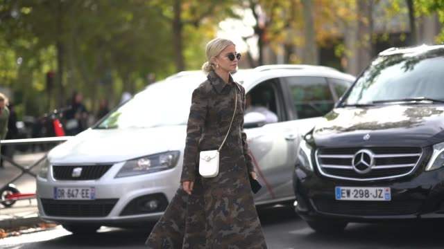 vídeos y material grabado en eventos de stock de caroline daur wears sunglasses, a earrings, a military camouflage print long coat, a white bejewelled bag, outside miu miu, during paris fashion week... - vestimenta para mujer