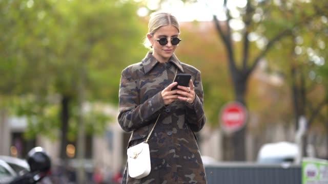 vídeos de stock, filmes e b-roll de caroline daur wears sunglasses, a earrings, a military camouflage print long coat, a white bejewelled bag, outside miu miu, during paris fashion week... - celebrities