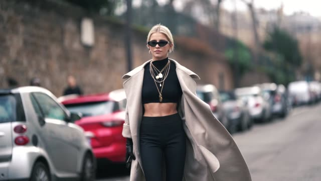 caroline daur wears sunglasses, a gray long coat, a black crop top, dark pants, several necklaces, earrings, outside elie saab, during paris fashion... - street style stock videos & royalty-free footage