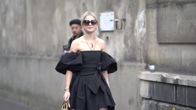 caroline daur wears sunglasses, necklaces, a black off-shoulder gathered dress, a red valentino bag, black valentino pointy kitten heeled slingback... - street style stock videos & royalty-free footage