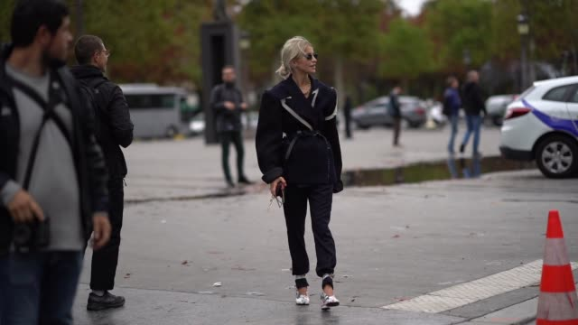 stockvideo's en b-roll-footage met caroline daur wears sunglasses, necklaces, a navy blue oversized jacket with apparent seams and ripped hem white inserts, a black belt, a red mini... - zoom out