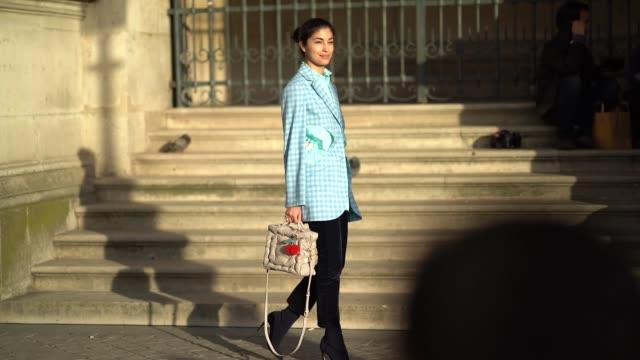Caroline Issa wears a blue checkered blazer jacket a bag black croped flare pants black shoes outside Louis Vuitton during Paris Fashion Week...