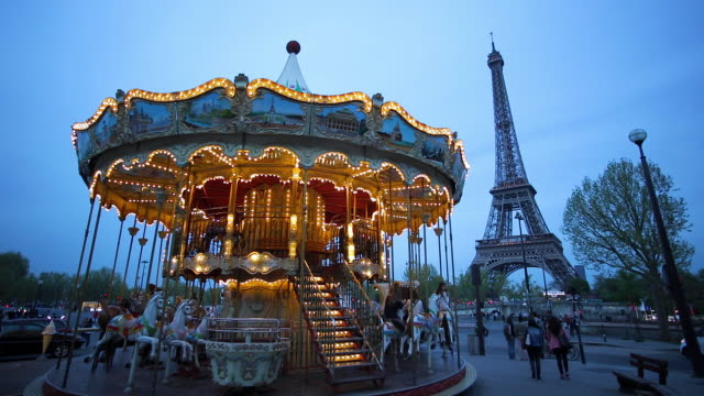 carousel below the eiffel tower at twilight, paris france - eiffel tower stock videos and b-roll footage