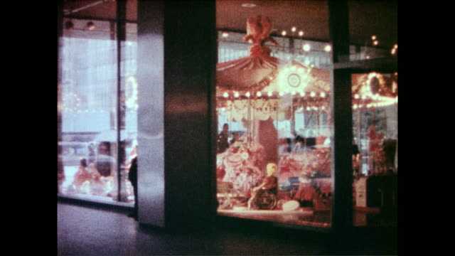 carousel inside store viewed through store window / cu of toys seated on carousel horses / silhouettes of children watching watching the carousel on... - 1954 stock videos and b-roll footage
