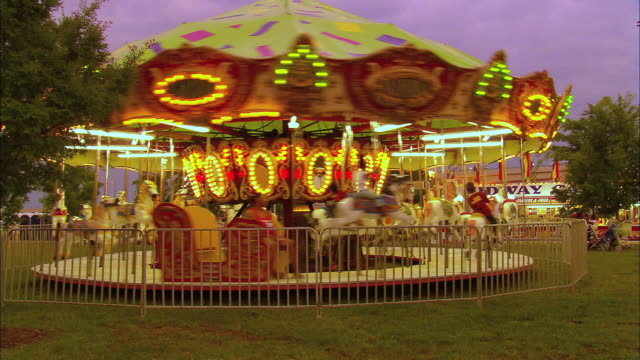 carousel with family of four riding; evening - familie mit drei kindern stock-videos und b-roll-filmmaterial