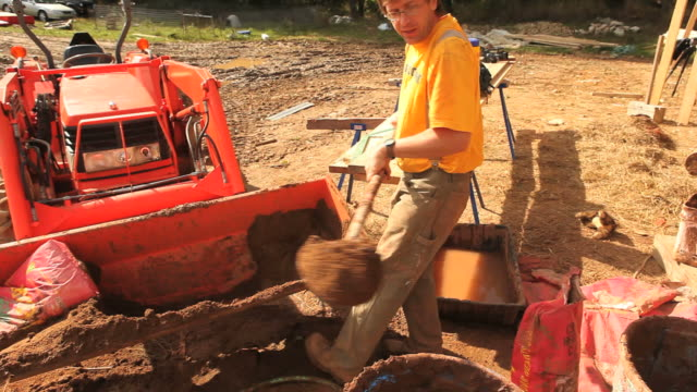 ms carpenter adding clay into adobe mud mixture during  framing of an energy efficient post / grass lake, michigan, usa    - adobe material stock videos and b-roll footage