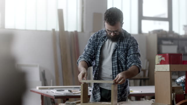 carpenter assembling piece of furniture - carpentry stock videos & royalty-free footage