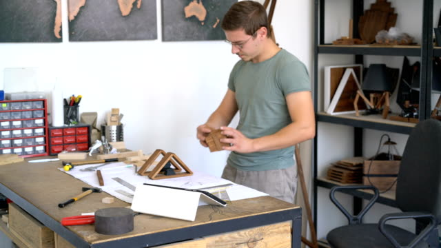 Carpenter assembling wooden project and looking at his tablet.