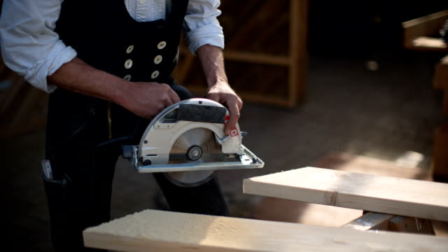 carpenter at work with the portable circular saw - hochgekrempelte ärmel stock-videos und b-roll-filmmaterial
