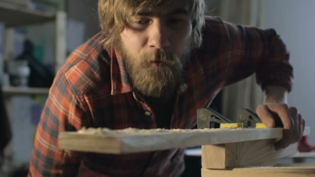 Carpenter blowing shavings off wood
