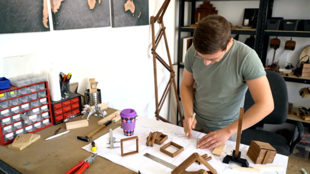 carpenter building wooden product in his workshop - drawing artistic product stock videos and b-roll footage