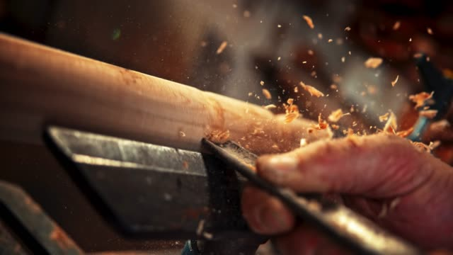 slo mo carpenter chiseling a rotating piece of wood and particles are flying around - chisel stock videos and b-roll footage