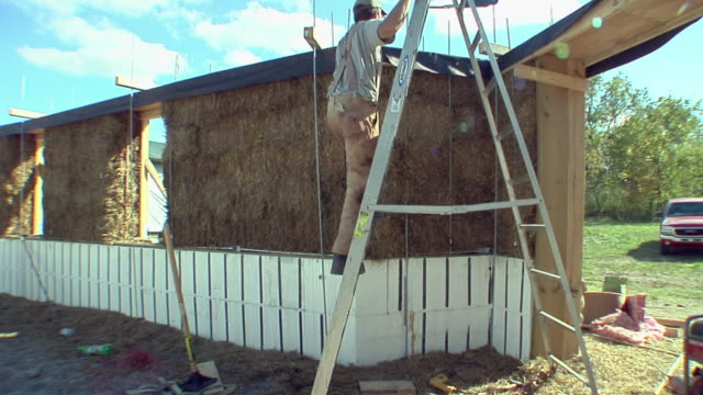 vidéos et rushes de ws carpenter climbing ladder and working on top of wall of straw house under construction, grass lake, michigan, usa - échelle