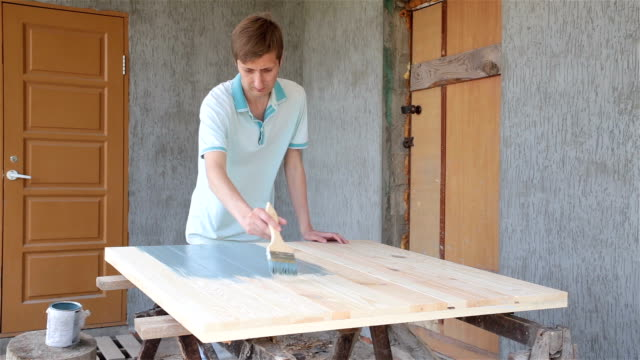 Carpenter covers the wooden surface with blue paint.