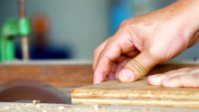 Carpenter cutting a wooden plank in workshop