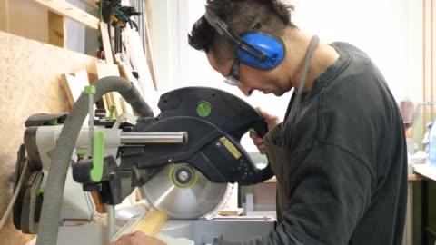 stockvideo's en b-roll-footage met timmerman die hout met een cirkelzaag snijdt - work tool