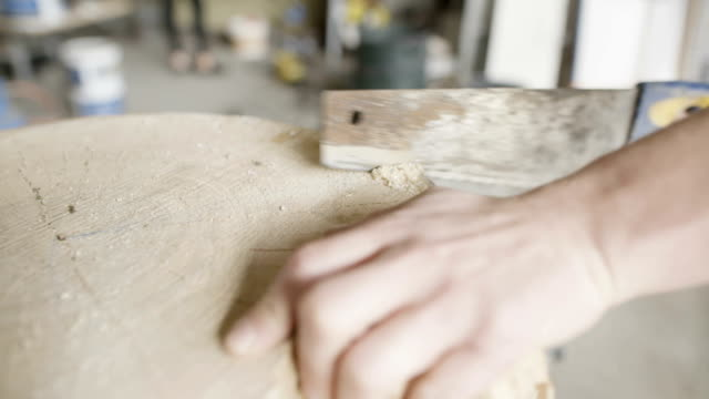 Carpenter Cutting Wood With Handsaw In Workshop
