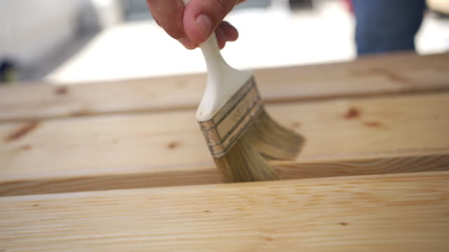carpenter doing wood care outdoors - wood material stock videos & royalty-free footage